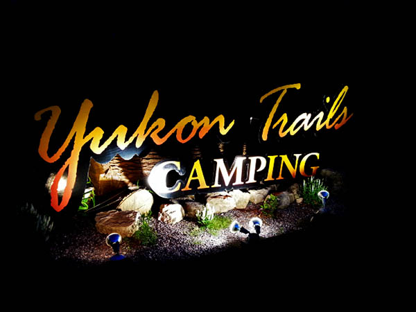 Yukon Trails sign at night.