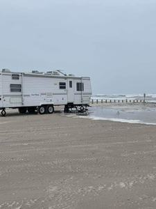 RV camping on the beach where a travel trailer is being consumed by the tide.